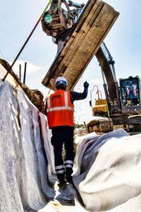 Dans cette photographie de suivi de chantier, un ouvrier casquée guide par ses gestes un tracts-elle qui déverse dans une tranchée un lit de graviers lors du chantier de réfection de la RN 165 à la sortie de Nantes en direction de Vannes