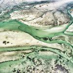 L'estran de la baie de Quiberon laisse apparaître de biens étranges formes. L'eau a creusé des sillons dans lesquels s'engouffrent des bras d'eau coloré. Les quelques cailloux couverts de moules, bigorneaux et quelques teintent de foncés le fond de la photo et donne un aspect quasi dramatique à celé-ci