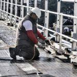 Un ouvrier étancheur est en train de souder une membrane bi-couche d'étanchéité sur une toiture à Angers. Il porte ses EPI, gants, lunettes, et protection-bouchon d'oreilles.