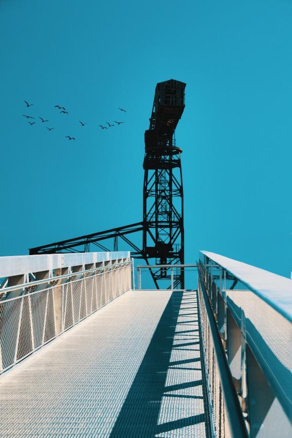 La grue noire sur un fond bleu électrique (le ciel) depuis le ponton menant à l'embarcadère du Navibus et du Passe-Partout. Ce dernier fait désormais partie du voyage à Nantes