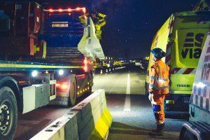 """Photographies de nuit prise lors d'un suivi photographique et reportage de chantier nocturne. Un homme en orange de la société Esvia, attend qu'un camion muni d'une grue dépose une BT4- Il s'agit d'une glissière de sécurité destinée à séparer une voie en travaux de la route dite """"normale"""". Pendant toute la nuit, ils vont déposer ces glissières en béton afin de faciliter les travaux de création d'une nouvelle voie en direction de Vannes. Les cônes orange sont de sortie."""