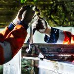 Photographies de nuit réalisées lors d'un suivi de chantier en Vendée. Deux hommes en orange tiennent un outil entre leurs mains. Chacun a besoin de l'effort de l'autre. Ils ne peuvent y arriver que quand l'autre exerce une force. Des boulons de gros diamètres sont ainsi serrer manuellement.