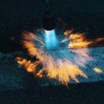 photo prise lors d'un suivi nocturne de chantier. Un ouvrier est en train de passer le chalumeau sur une bande blanche de marquage au sol. L'objectif est d'effacer le marquage temporaire en orange, pour ne laisser place qu'au marquage blanc. Le bleu du gaz qui s'échappe du chalumeau brille de mille feux dans la nuit.