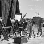 Une photographie en noir et blanc. Sur une scène installée à la campagne, des instruments à vents attendent leurs musiciens. Posés à l'envers, sortie contre terre, les notes blanches, les notes noires se sont tuent. Et comble du comble, même les silences sont réduits au silence.