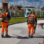 Deux hommes en orange sont équipés de souffleuses. Alors que le tramway très coloré d'Angers s'approche de son arrêt place Terra Botanica, ils soufflent le surplus de gravillons qu'ils viennent de fixer au sol à l'aide d'une résine afin de dessiner un béton matricé.