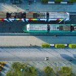 Vue aérienne de deux tramways très colorés de la ville d'Angers. Vue zénithale au niveau d'un arrêt de tram, comme on a coutume de dire. On peut clairement distinguer cet axe multi-modale entre les transports publics, et le partage de la route entre cyclistes et voitures. Nous sommes ici en zone 30, et pour cette raison, il n'y a pas de passage piéton.