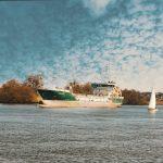 Dans cette photo prise depuis les quais du Pellerin à proximité de Nantes, deux bateaux se livrent une course dont l'issue est déjà connue. UN gracier croise la course d'un voilier qui semble si petit à son côté. Le ciel est rempli de nuages moutonneux et le fier clocher de la ville de Couëron domine la Loire.
