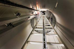 Un homme du GRIMP monte à l'échelle. Cette échelle de 30 mètres de haut située au coeur d'une éolienne permet d'accéder à un ascenseur.