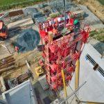 Coulage d'un béton dit décarboné sur un bâtiment en construction. Le camion pompe alimente cette gigantesque tour de métal destinée au coffrage.