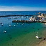 Vue aérienne de Port-Maria à Quiberon. Quelques bateaux de pêche sont amarrés. Au fond dans un ciel d'un bleu intense on distingue Belle-île en Mer et le château Turpault. L'eau est translucide et oscille entre le vert et le bleu. Les Caraïbes ? Non la Bretagne